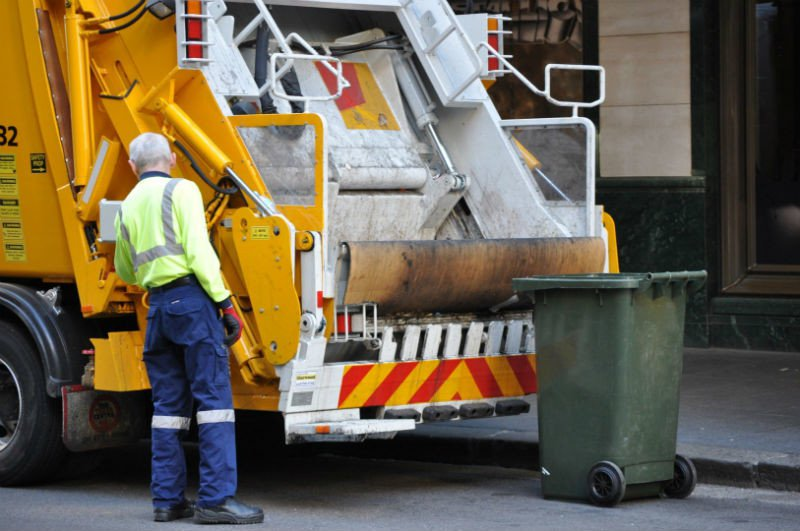 Man disposing of waste in a bin lorry