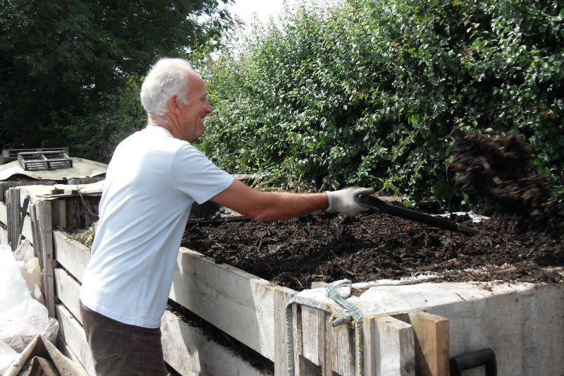 Man shovelling soil for compost