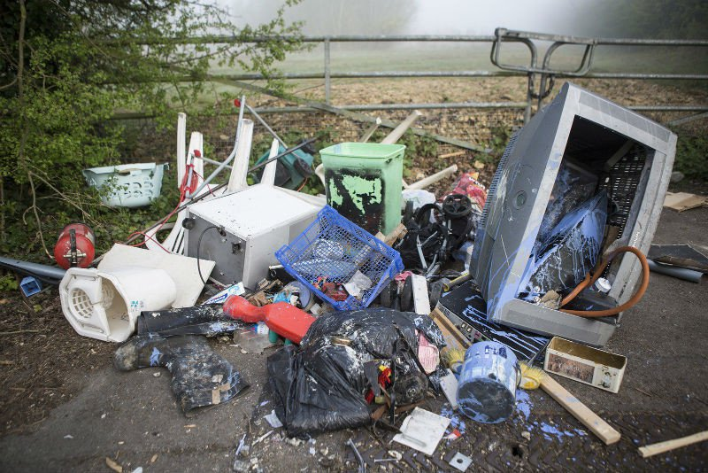 Collection of fly-tipped rubbish on the ground outside